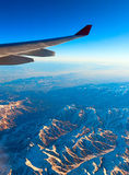 Air travel over the mountains. The wing of an airliner Royalty Free Stock Photo