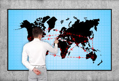 Air travel scheme. Businessman pointing to plasma panel with air travel scheme Royalty Free Stock Photography