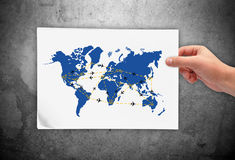 Air travel scheme. Hand holding paper with air travel scheme Royalty Free Stock Photography