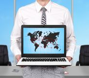 Air travel scheme. Young businessman holding laptop with air travel scheme Royalty Free Stock Images