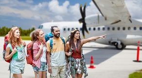 Friends with backpacks over plane on airfield Royalty Free Stock Photography