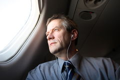Air Traveller. Looking out of airplane, listening to audio with earphones Royalty Free Stock Images