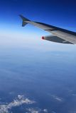 In the Air (upper). Left wing of the aircraft in the air over clear sky above and some clouds below. Free space for custom text below the wing Royalty Free Stock Photo