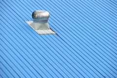 Air vents on top of a blue roof stock image