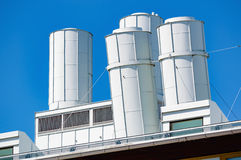Air vents. On top of an industrial building. Some of the vents are slightly tilted. White metal against a clear blue sky Stock Photo