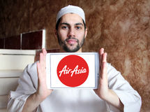 Airasia airlines logo. Logo of airasia airlines on samsung tablet holded by arab muslim man Royalty Free Stock Images