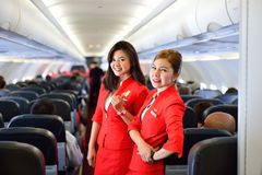 AirAsia crew members. SINGAPORE - NOVEMBER 04, 2015: AirAsia crew members on board of Airbus A320. AirAsia is a Malaysian low-cost airline headquartered near Royalty Free Stock Photos