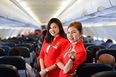 AirAsia crew members. SINGAPORE - NOVEMBER 04, 2015: AirAsia crew members on board of Airbus A320. AirAsia is a Malaysian low-cost airline headquartered near Stock Photo
