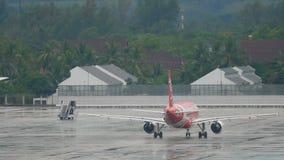 AirAsia-vliegtuig die op natte schort taxi?en stock video
