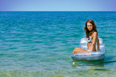 Airbed. Young woman sitting on the airbed royalty free stock image