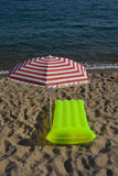 Airbed and sun umbrella on a beach. Green airbed lying on a sand near sun umbrella on a beach in Costa Brava - Spain Royalty Free Stock Image