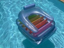 Airbed in swimming pool. An empty blue airbed in a swimming pool royalty free stock photo