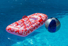 Airbed and Water Ball in Swimming Pool. Airbed and Water Ball Floating in Swimming Pool stock images