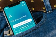Airbnb在苹果计算机iPhone x屏幕特写镜头的应用象在牛仔裤装在口袋里 Airbnb app象 Airbnb com是网上网站 免版税库存照片
