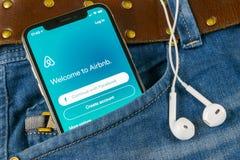 Airbnb在苹果计算机iPhone x屏幕特写镜头的应用象在牛仔裤装在口袋里 Airbnb app象 Airbnb com是booki的网上网站 库存照片