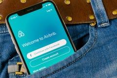 Airbnb在苹果计算机iPhone x屏幕特写镜头的应用象在牛仔裤装在口袋里 Airbnb app象 Airbnb com是booki的网上网站 免版税库存照片