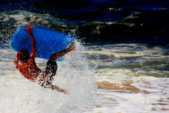 Airborne. Kid flipping in midair after hitting a wave on his boogie board in Hawaii Stock Image