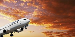 Airborne airliner in flight with yellow altocumulus cloud in sun royalty free stock images