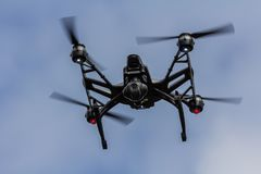Airborne drone quadcopter. Airborne drone viewed from below against blue sky stock images