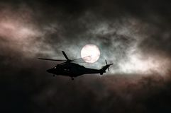 Airborne Helicopter in storm cloud sunset silhouette stock images