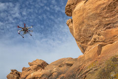 Airborne hexacopter drone. FORT COLLINS, CO, USA, February 12, 2015: DJI F550 Flame Wheel hexacopter drone is flying with a camera along sandstone cliff stock photo