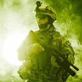 Airborne infantry. United States paratrooper airborne infantry in the smoke stock photography
