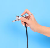 Airbrush in hand over blue background Royalty Free Stock Images