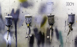 Airbrushes for car painting on color stained gray wall. Four airbrushes on wall stained with paint royalty free stock photo