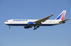 The Airbus company the Boeing 777-300 Transaero (EI-UNE) in the air on blue sky background Royalty Free Stock Photography