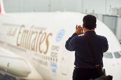 Airbus A380. HONG KONG - MARCH 09, 2015: a man taking photo of docked Airbus A380. The Airbus A380 is a double-deck, wide-body, four-engine jet airliner Royalty Free Stock Images