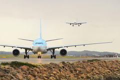 Airbus A330 on runway with second plane landing behind Royalty Free Stock Photo