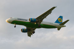 Airbus A320-214 (UK-32020) of the company Uzbekistan Airways in cloudy sky Royalty Free Stock Photography