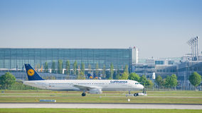 Airbus A321 von Lufthansa-Fluglinien, die auf Rückstellungsschlepper mit einem Taxi fahren Lizenzfreie Stockfotografie