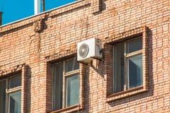 Airconditioner op de muur van een baksteengebouw tussen de vensters op de hoogste vloer Royalty-vrije Stock Afbeeldingen