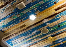 Airconditionermasker en verlichting op het plafond dat met oude houten panelen en schilverf verfraaide royalty-vrije stock fotografie