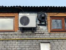 Airconditioning op een bakstenen muur met kleine vensters Stock Afbeeldingen