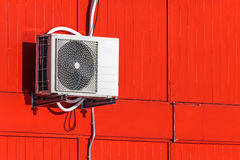Airconditioning unit on a red wall. Exterior airconditioning unit on a red wooden wall Stock Image