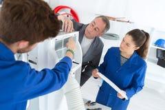 Airconditioningsleerlingen die aan compressor werken stock foto