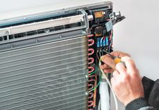 Airconditioningstechnicus en a-een deel van het voorbereidingen treffen stock foto