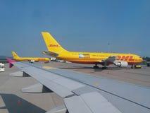 Aircrafst da empresa do enviamento de DHL estacionado no aeroporto com canela do passageiro fotos de stock