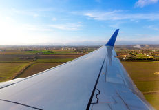 Aircraft airplane wing in landing process. In blue sky day Stock Image