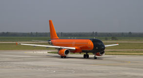 Aircraft in the airport. Orange and black aircraft docked in airport Royalty Free Stock Image