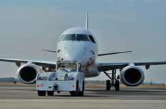 Aircraft at airport. Aircraft taxiing for departure being pushed backwards by a ground support vehicle royalty free stock photos