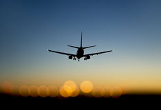 Aircraft approaching airport at sunset Stock Photography