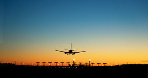 Aircraft approaching airport at sunset Royalty Free Stock Photography