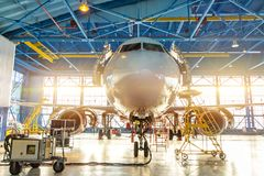 Aircraft in the aviation industrial hangar on maintenance, outside the gate bright light.  stock photo