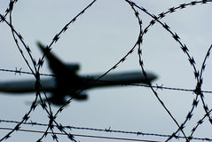 Aircraft and barbed wire. Closeup of barbed wire fence with flying aircraft silhouetted in background Stock Photos