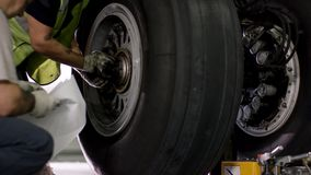 Aircraft brake repair. Close up of airplane wheel and shaft. Huge airplane tyre with shaft and landing gear of plane Royalty Free Stock Photography