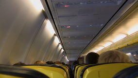 Aircraft cabin in flight. Inside passenger aircraft cabin in flight. View from rear stock video footage