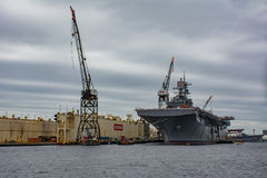 Aircraft carrier Moored dockside  by large Crain Royalty Free Stock Photography